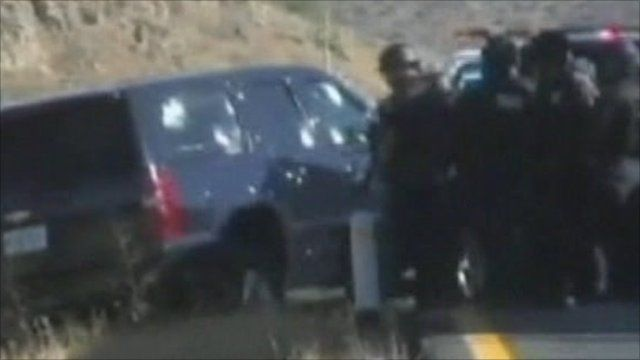 Police officers look at car with bullet holes