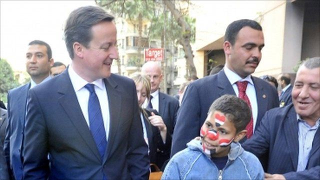 Prime minister David Cameron meets Mohammed, 15, during a walk through the streets around Tahrir Square in Cairo, Egypt.