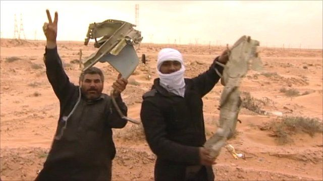 Rebels hold wreckage from a fighter bomber from Colonel Gaddafi's airforce