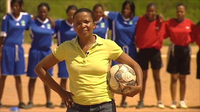 A woman holding a football in front of a female football team