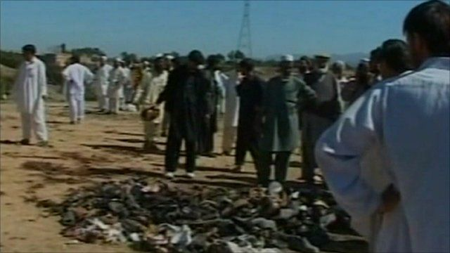 Mourners survey the debris left after the attack