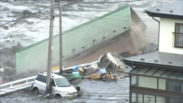 A building is swept away by the tsunami