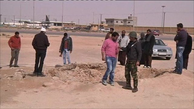 People surrounding crater in Ajdabiya