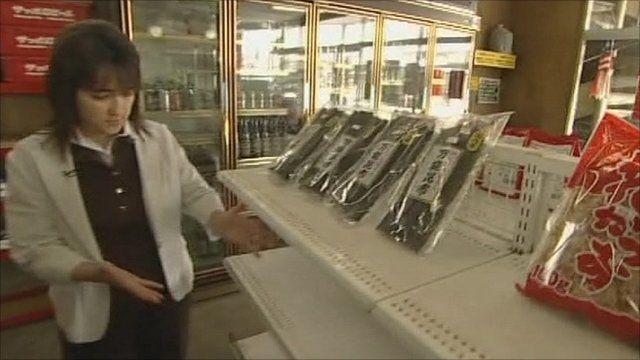 Shop owner stocks shelves in supermarket