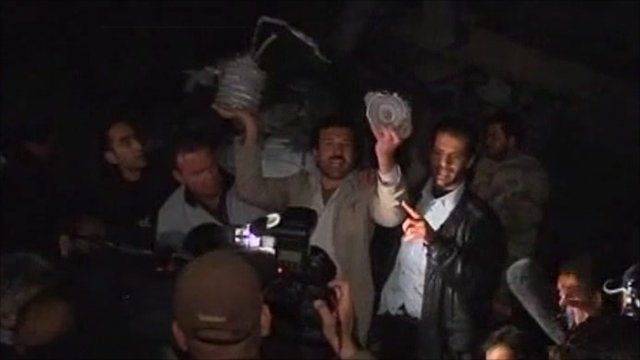 Men hold up debris claimed to be from coalition bombs to the press