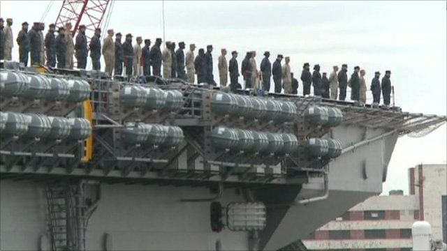 USS Bataan leaving port with people lined up on deck