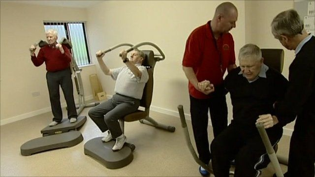 Dementia sufferers and care workers using gym equipment