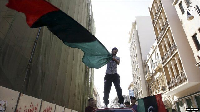 Person waving Libyan flag