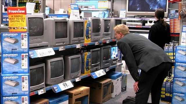 Man browsing televisions in an electrical goods store