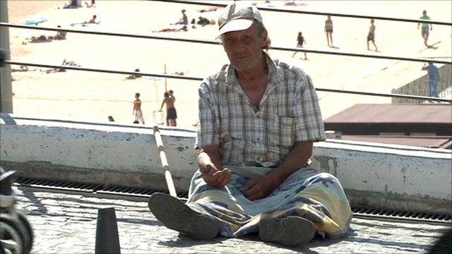 Portuguese man begging on beachfront