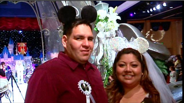 American couple in his and hers Disney mouse ears