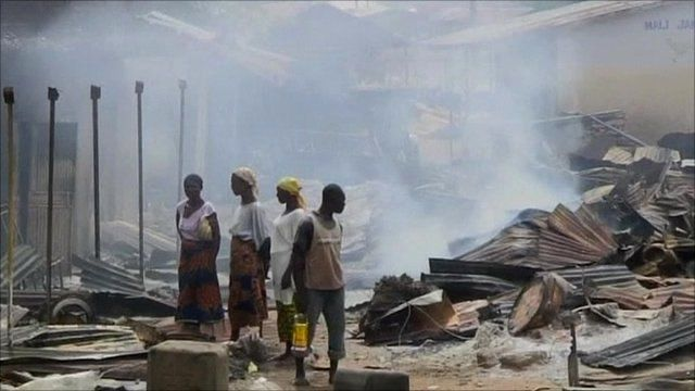 People standing in burned ruins of houses in Zonkwa