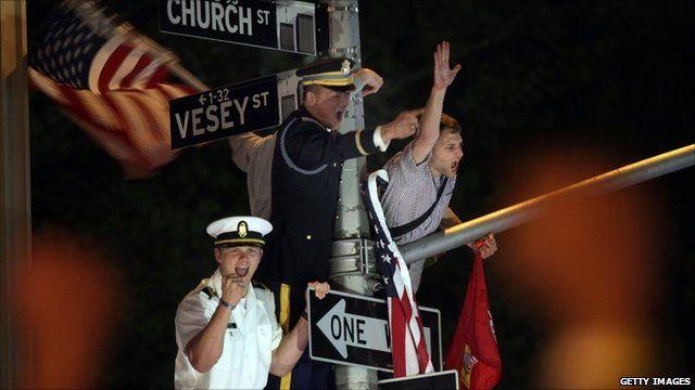 People climb lamp post in celebration