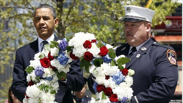 Barack Obama and a New York City firefighter carrying a wreath