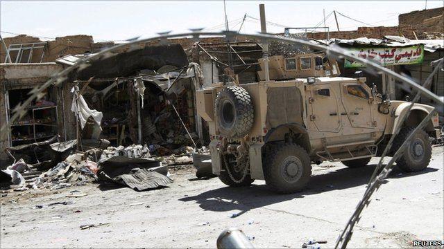US military vehicle drives past damaged buildings in Kandahar