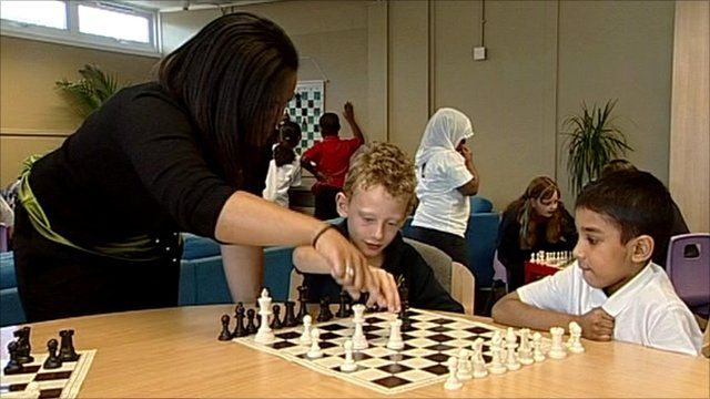 Teacher and pupils playing chess in school