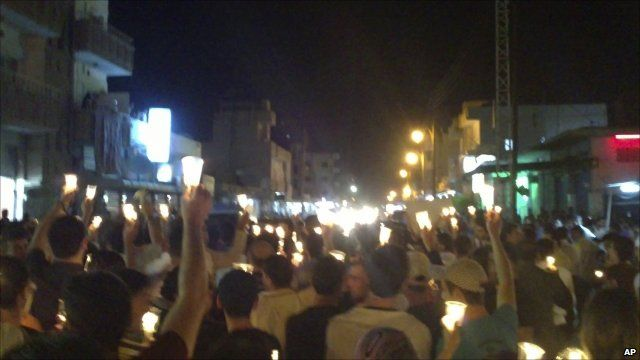 Anti-government protesters carry candles during a rally in the north-eastern city of Qamishli