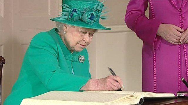 Queen signs visitors' book