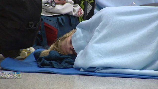 Woman sleeping on Edinburgh airport floor