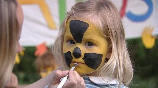 Girl have face painted with radioactive symbol