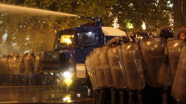 Riot police with a water cannon