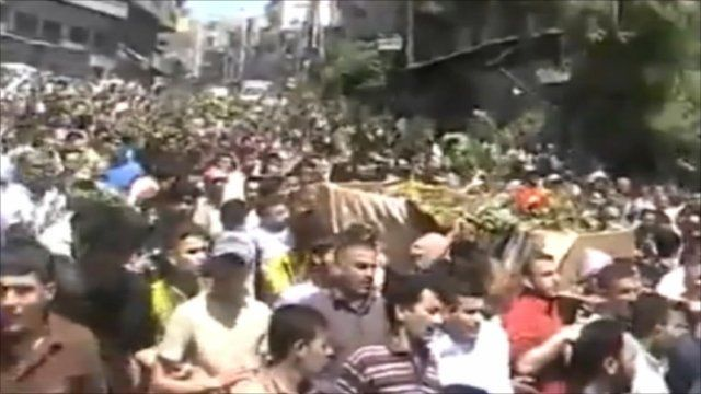Crowds surround a coffin being carried through the streets of Jisr al-Shughour