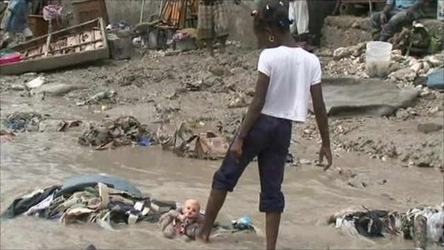 Girl playing with doll in floodwaters