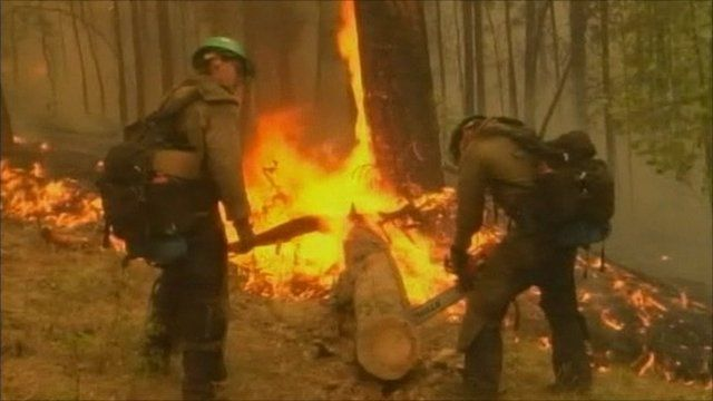 Fire crews clear vegetation from the path of the fire