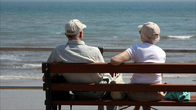 An elderly couple sitting on a beach