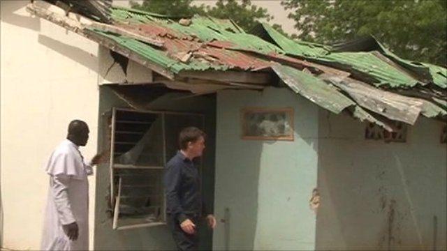 Jonah Fisher walking in front of badly damaged building, Maiduguri