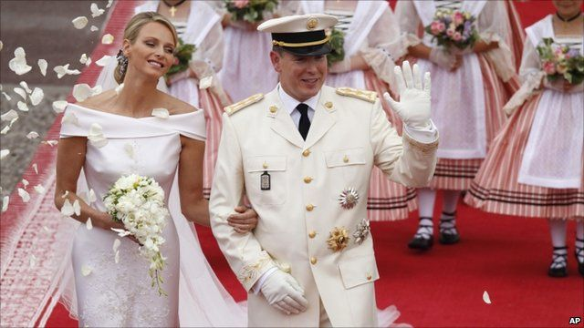 Prince Albert II waves to the crowd at the end of the religious ceremony, watched by his new wife, and Princess Charlene.
