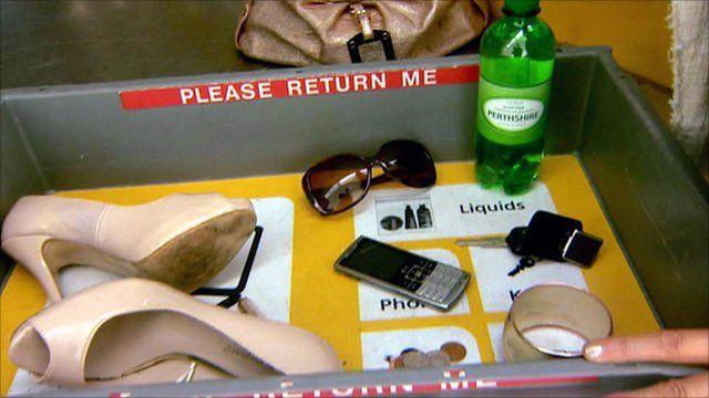 Airport security screening tray containing passenger belongings