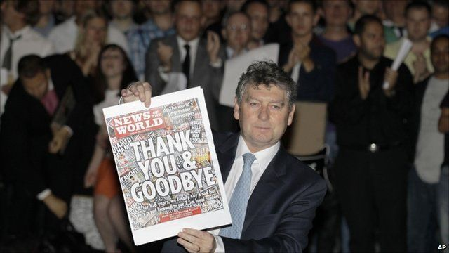 News o the World editor Colin Myler holds up the final edition of the paper