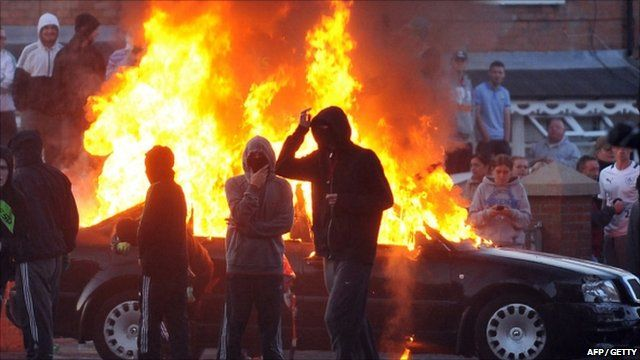 Masked youths in front of burning car