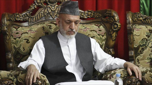 Afghan President Hamid Karzai attends a gathering after the burial ceremony of his brother Ahmad Wali Karzai