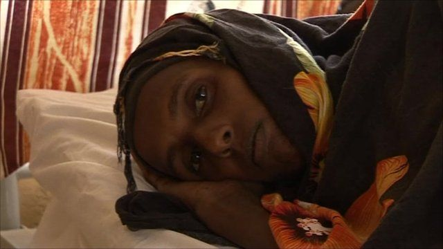 Woman lies on a bed in Kenyan refugee camp