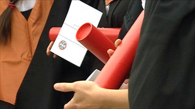 University graduates holding scrolls