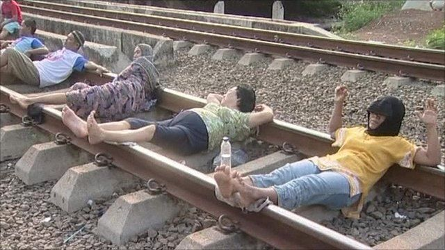 People lying down on a railway track