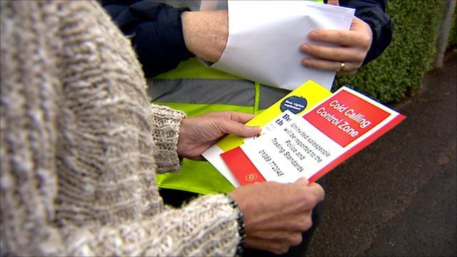 Woman holding a 'cold calling control zone' leaflet