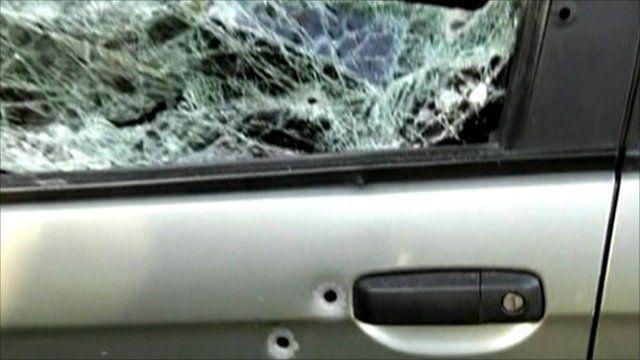 Bullet holes and damage to Patricia Acioli's car