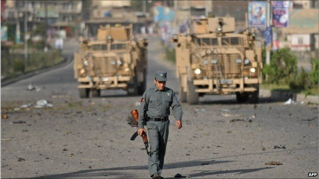 Afghan policeman walks in front of two British military vehicles at the site of a suicide attack in Kabul