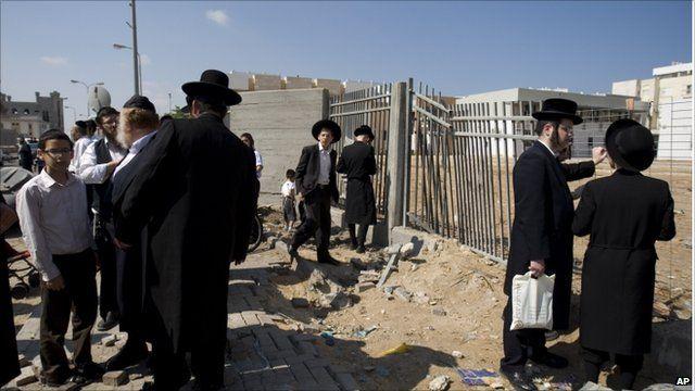 Israeli men by an area hit by rockets in Ashdod, Israel (19 August 2011)