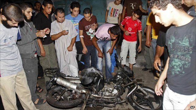 People look at damage to a motorbike in Gaza city