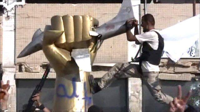 Rebels climb on statue in Gaddafi's compound