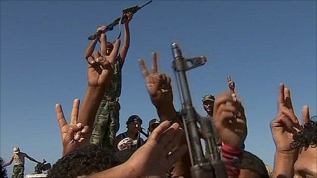 Rebel hold up their fingers in a peace sign in Libya