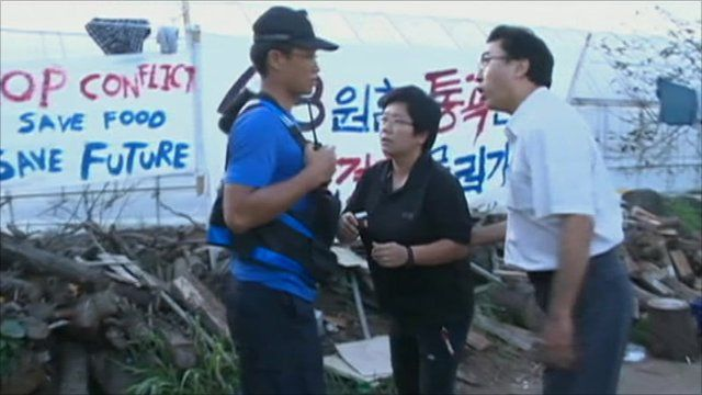 Protesters talking to security man outside Jeju protest camp