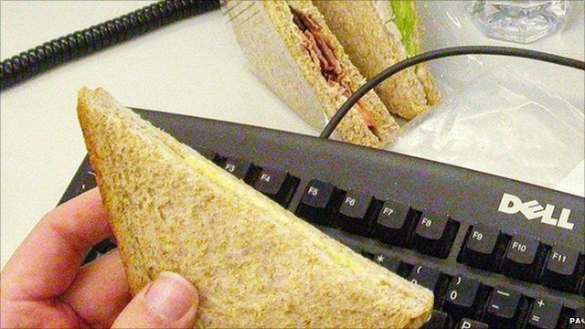 Man holding a sandwich over his computer keyboard