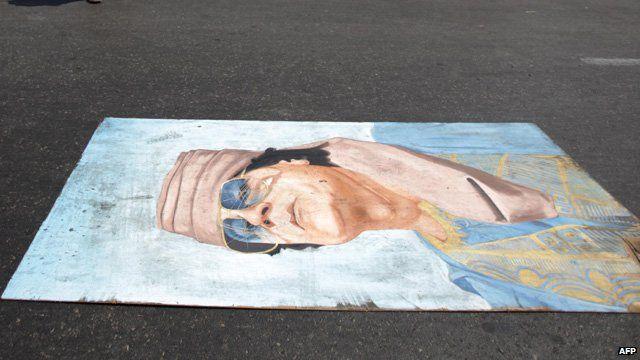 A portrait of Col Gaddafi lies on the street in Tripoli