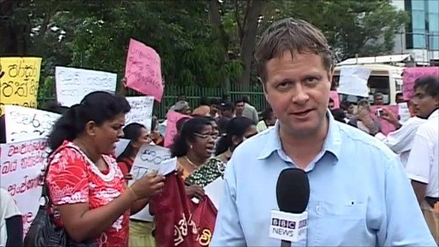 The BBC's Charles Haviland in front of protestors holding banners in western Sri Lanka