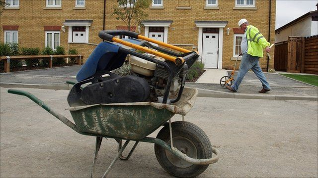 wheelbarrow and worker in yellow jacket